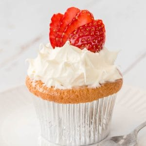 A baked cupcake in a foil patty pan, topped with whipped cream and strawberries