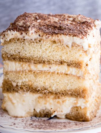 Close up shot of tiramisu showing three layers of coffee soaked biscuits and whipped cream.