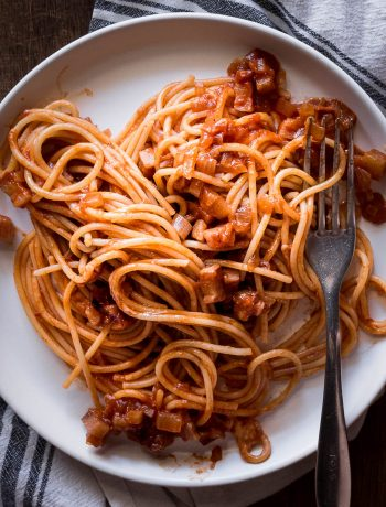 Bucatini all'amatriciana served up on a plate with a fork.