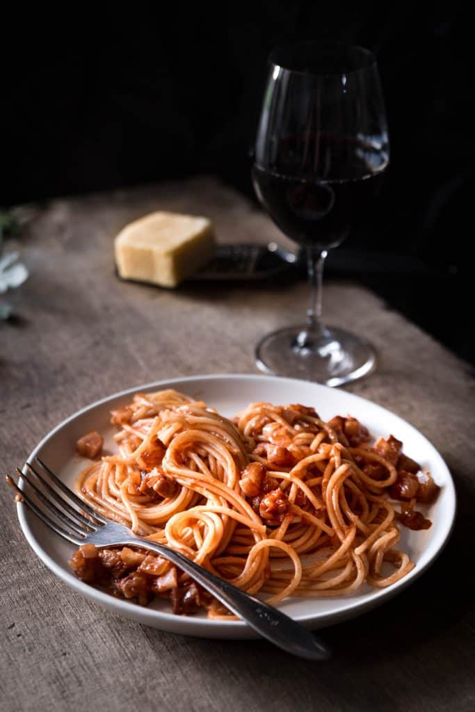 Plate of amatriciana pasta with cheese and wine in background.