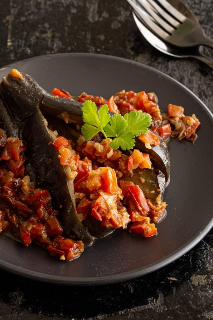 Burmese stuffed eggplant on a plate with tomato and shallot infused curry sauce.