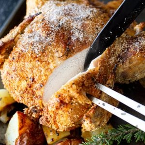Slicing into a roast chicken with crispy skin.