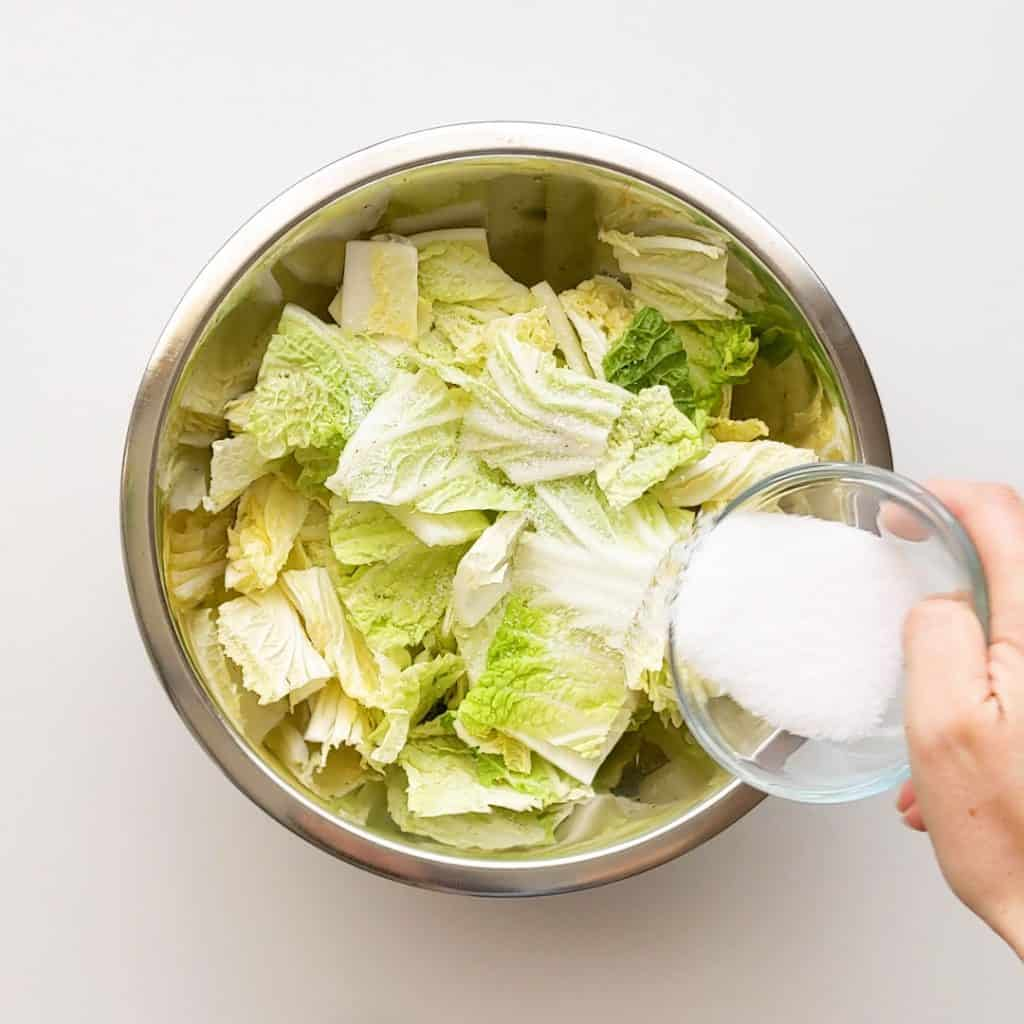 Pouring water on salted cabbage.