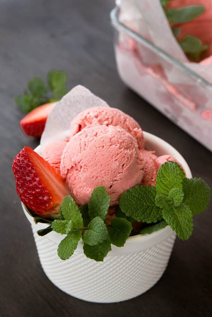 A bright pink scoop of strawberry ice cream in a white bowl with mint and fresh strawberries.