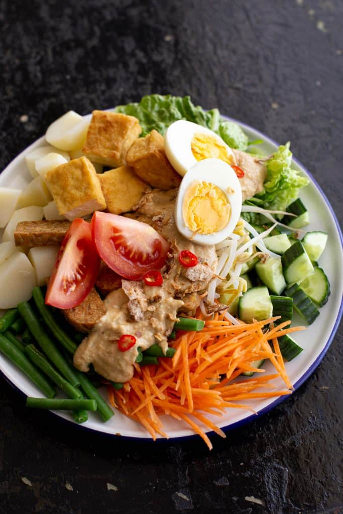 Fresh plate of Indonesian gado gado salad topped with peanut satay sauce.