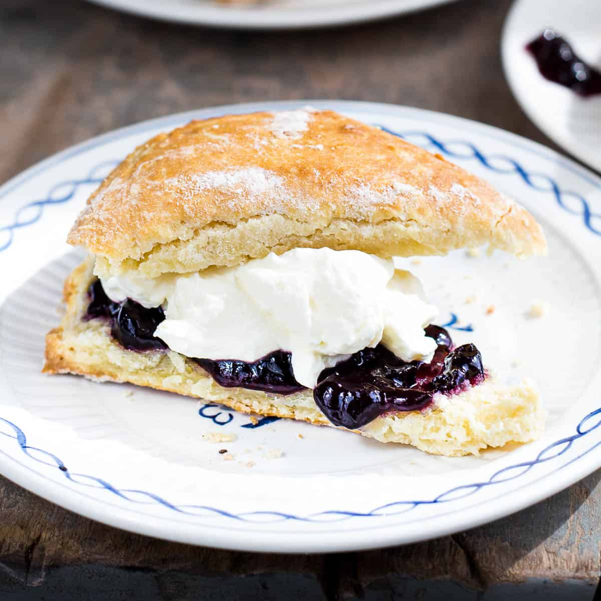 A fresh scone on a plate, filled with jam and cream.