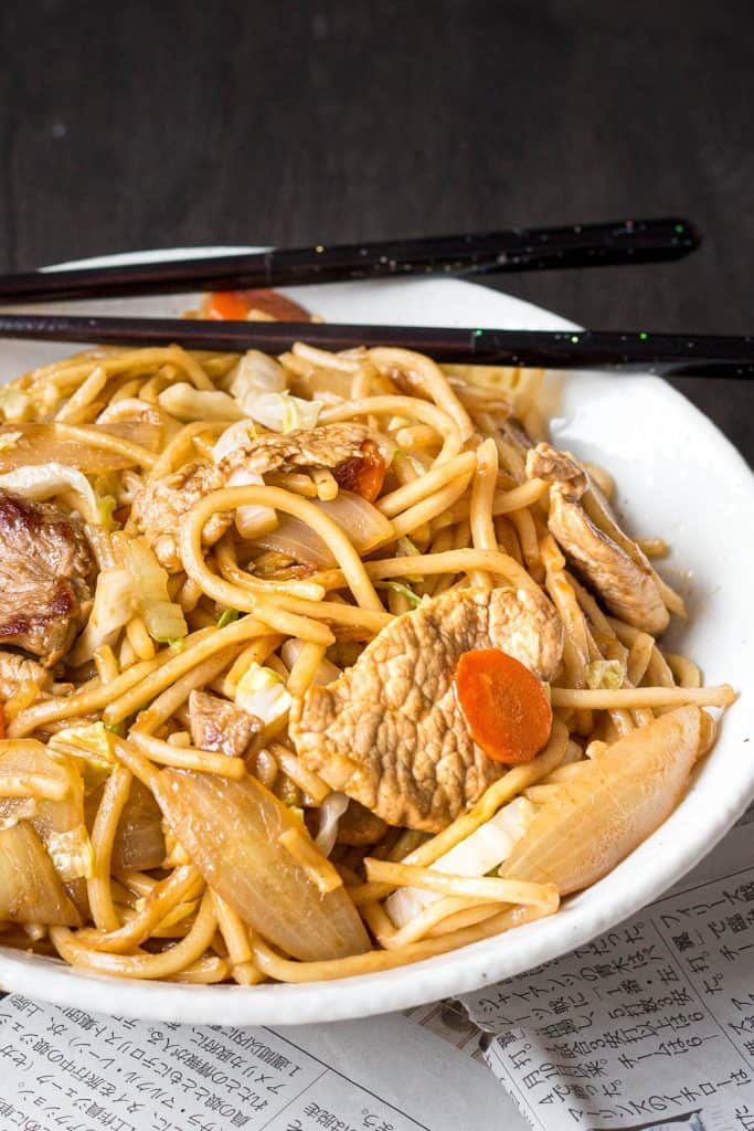 Bowl of yakisoba noodles with pork and carrot.