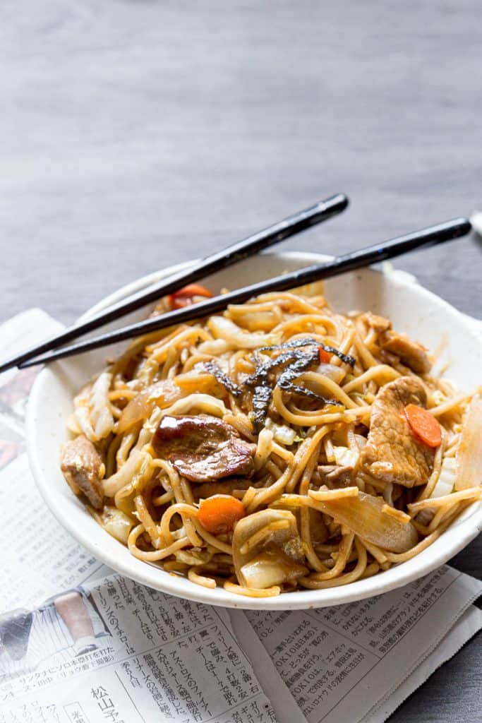 Bowl of stir fried Japanese noodles with chopsticks.