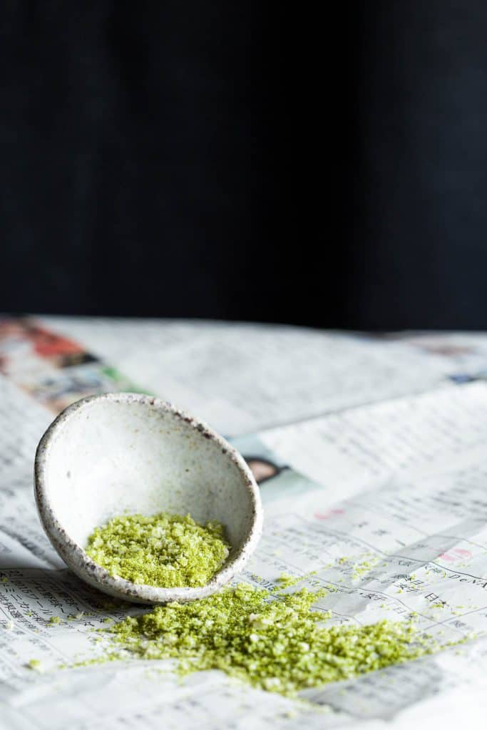 Seasoned salt with matcha green tea in a small pinch bowl with more of the blend spilt out the side.