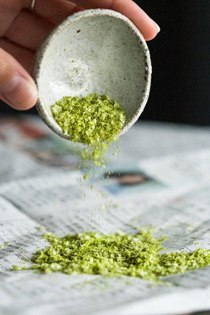 Pouring matcha salt onto a piece of newspaper.