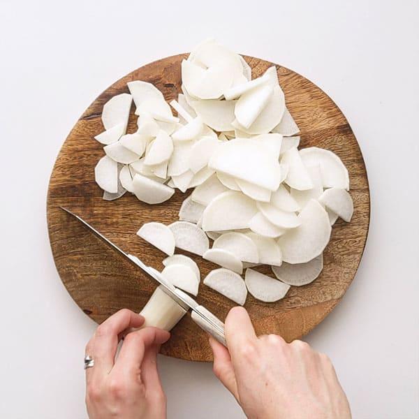 Slicing daikon radish ready for pickling.