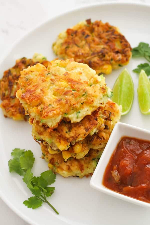Zucchini fritters with lime wedges and sauce.