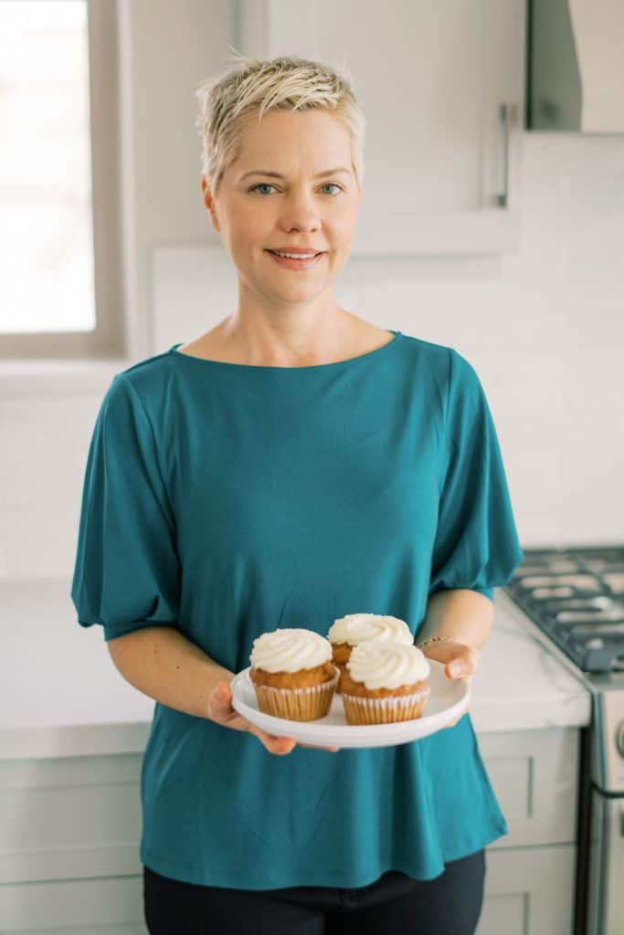 Carrie from Clean Eating Kitchen holding a plate of cupcakes.