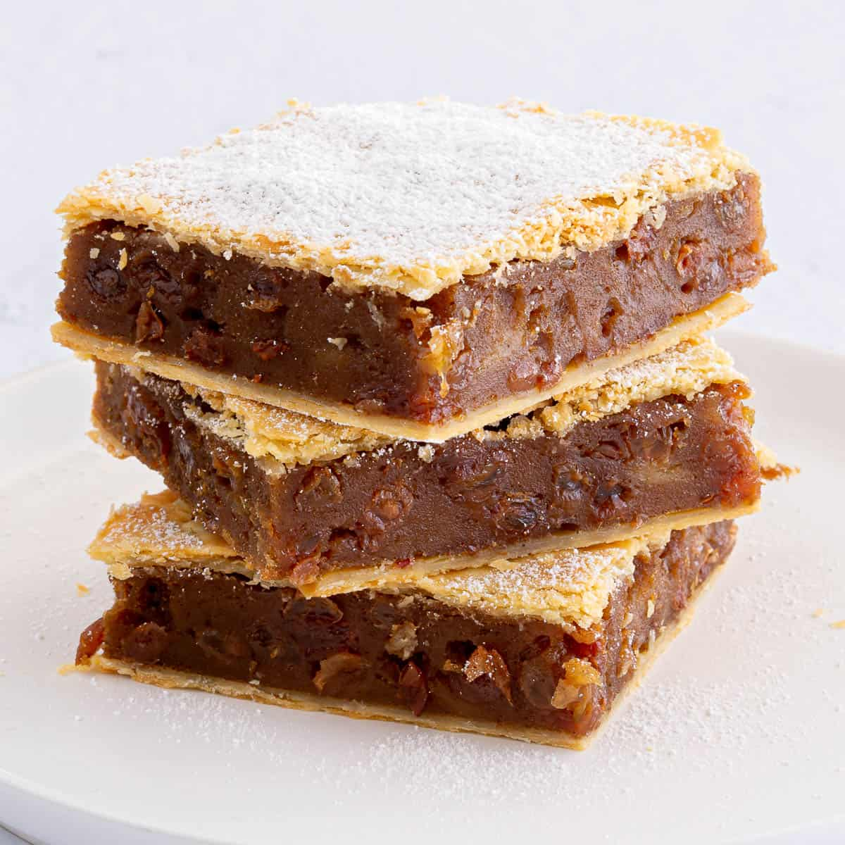 Stack of three slices of gur cake.
