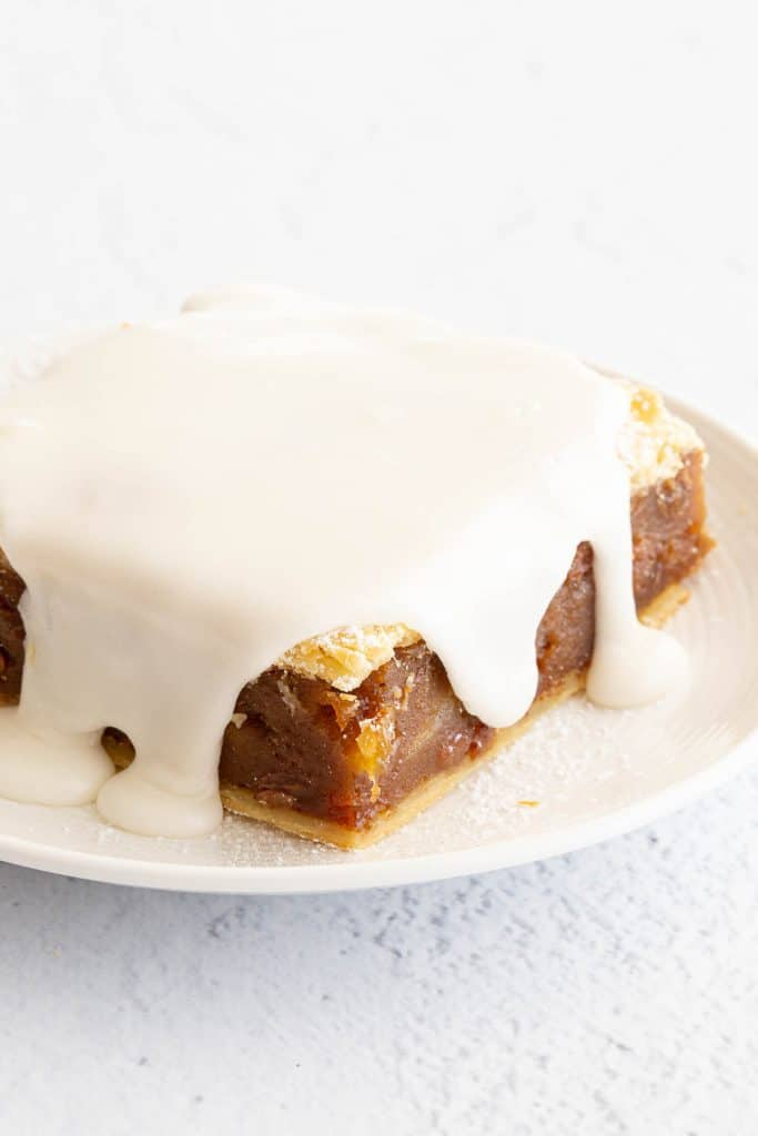 Vanilla icing smothered over a slice of gur cake.