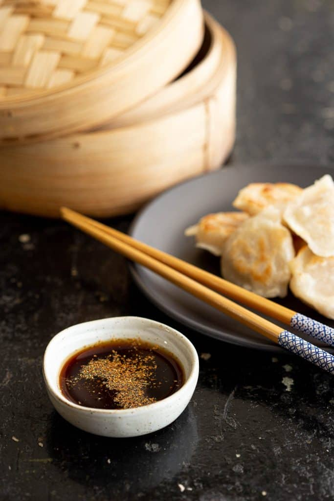 Dipping sauce with gyoza, chopsticks and steamer.