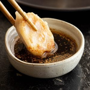 Gyoza being dipped into sauce with chopsticks.