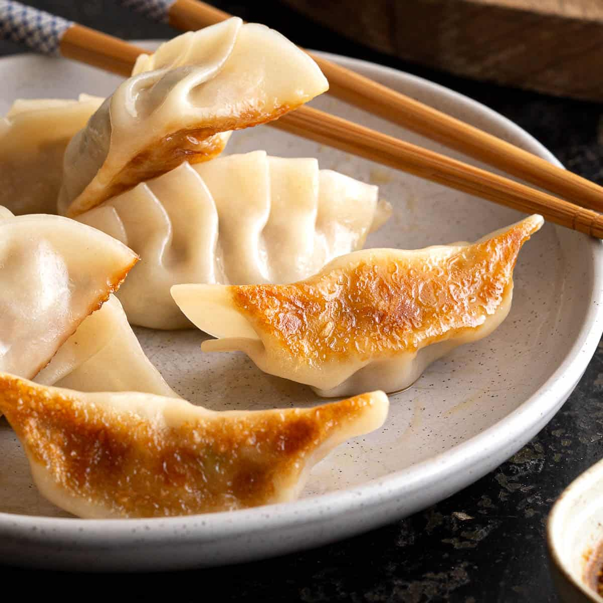 Crispy gyoza on a plate with dipping sauce.