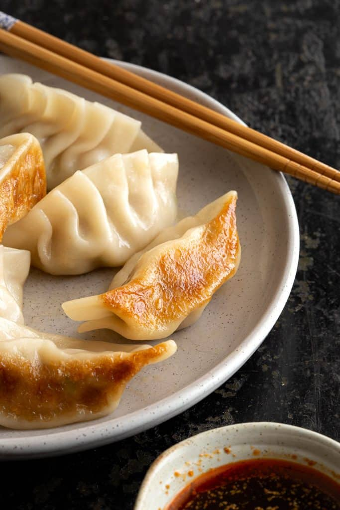 Freshly cooked gyoza on a plate with chopsticks.