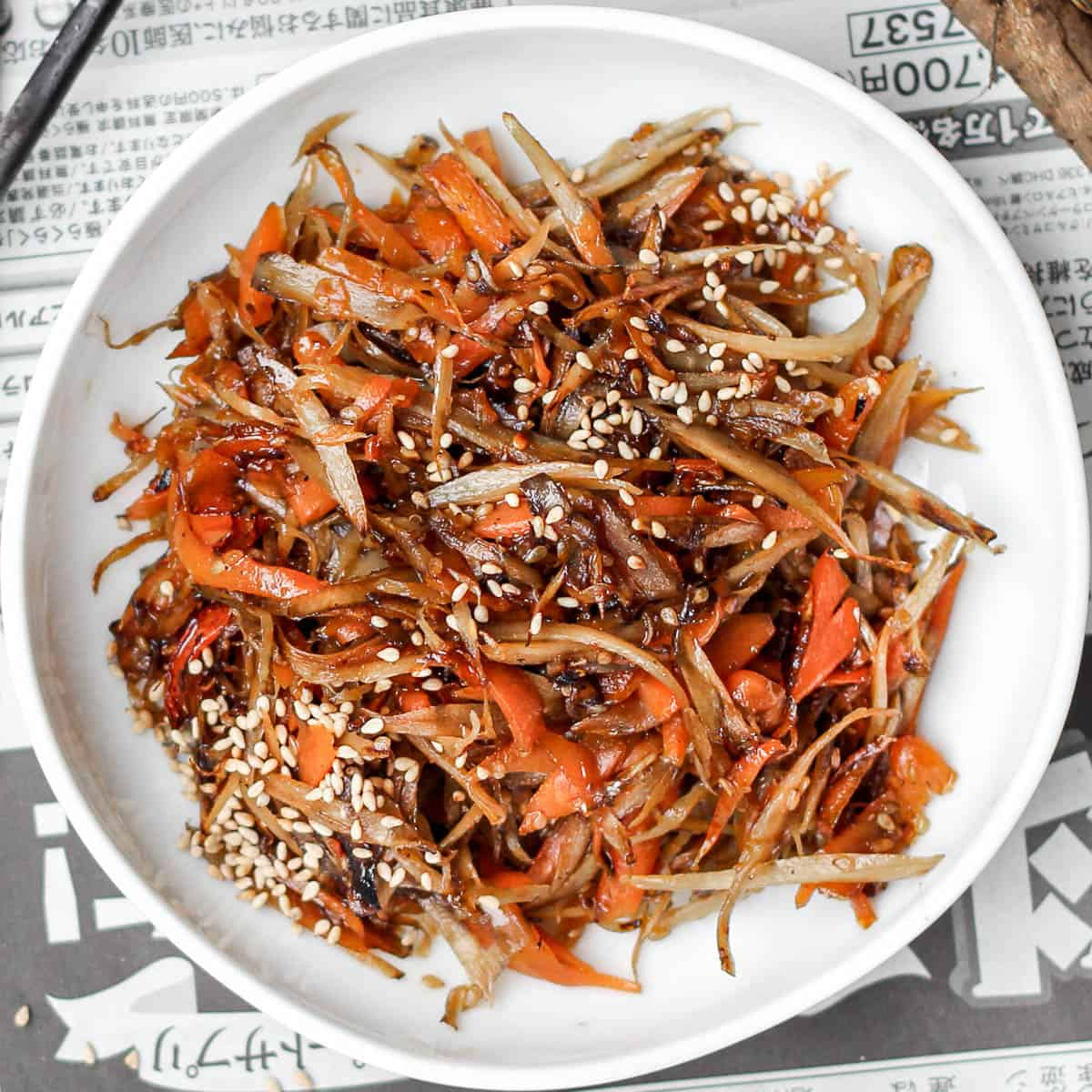 Stir fried carrot and burdock root (kinpira gobo) on a white plate.