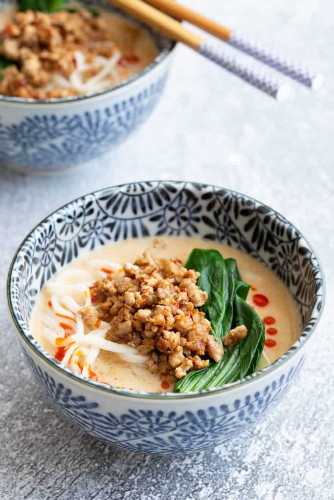A bowl of noodles in creamy sesame broth topped with crispy fried pork.