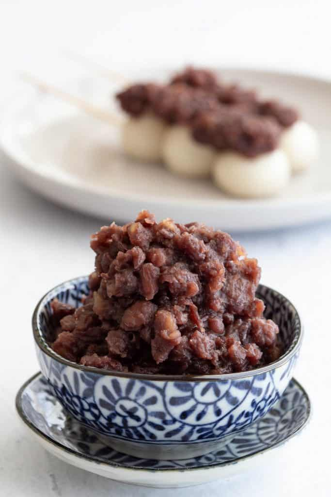 Bowl of sweet red bean paste with dango sticks in background.