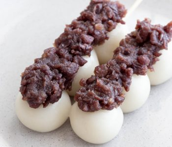 Rice flour dumplings topped with sweet bean paste on a stick.