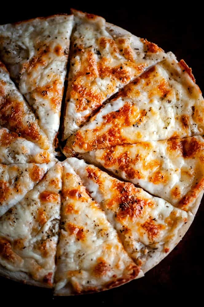 Sliced gluten-free pizza topped with cheese.