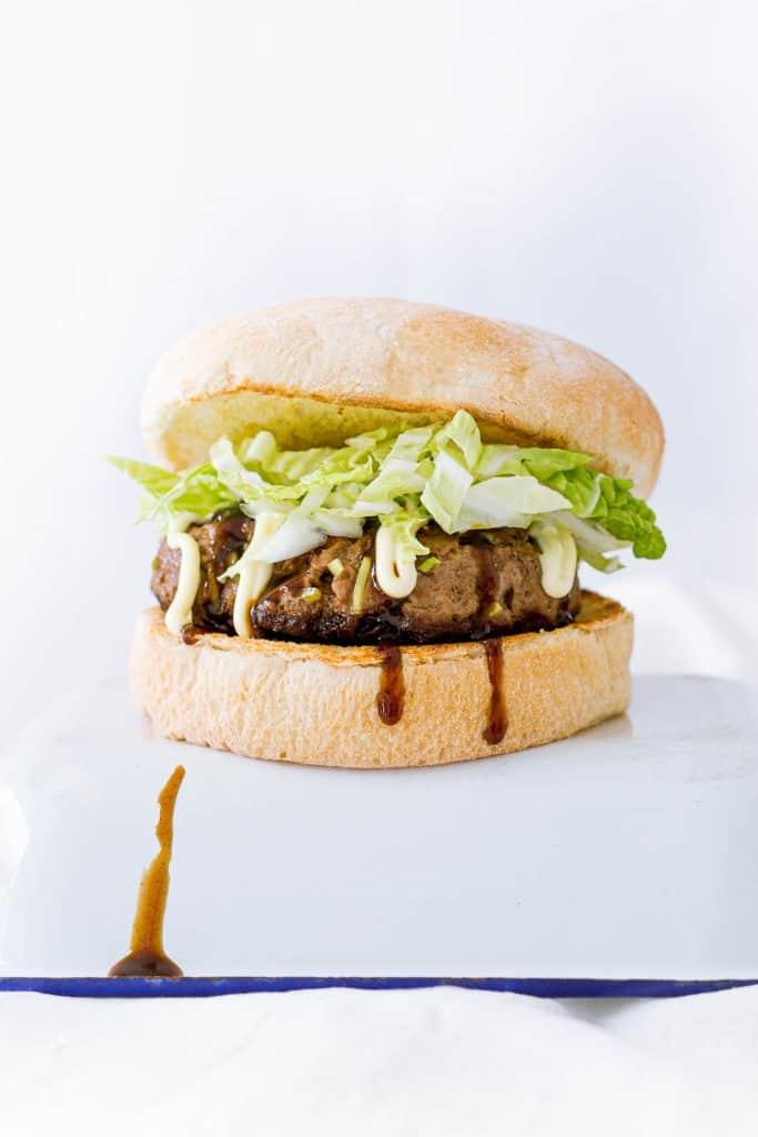 Japanese burger with bbq sauce running down the bun.