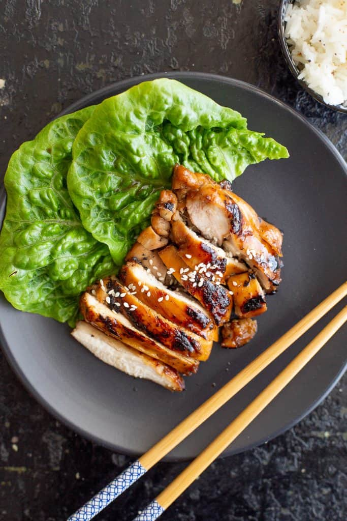 Top view of sliced chicken in a teriyaki sauce with lettuce and chopsticks.