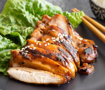 Slices of succulent teriyaki chicken with lettuce and chopsticks.
