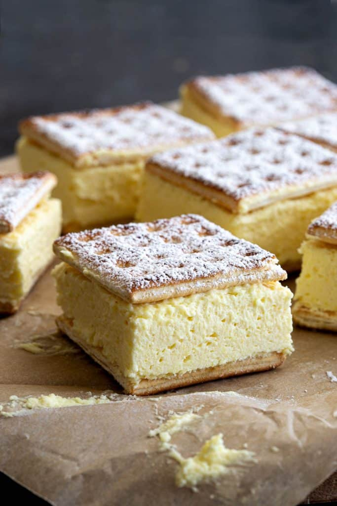 Close up view of a vanilla slice showing the creamy centre and icing sugar on top.