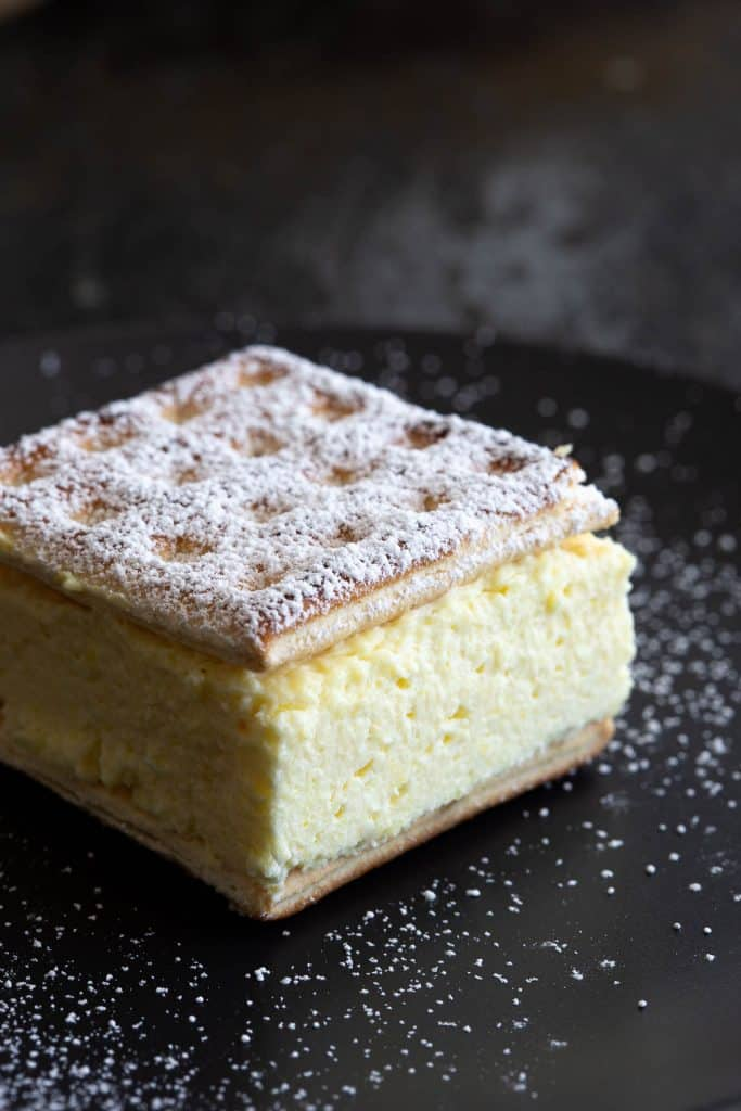 A vanilla slice on a black plate dusted with icing sugar.