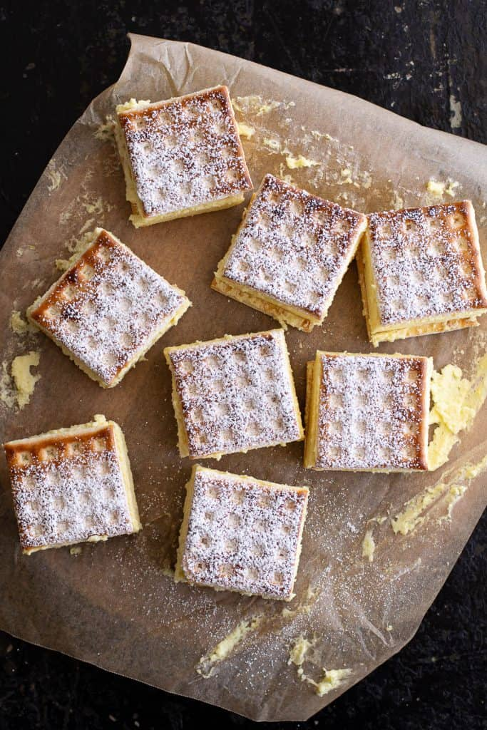 Top down view of vanilla slice pieces laid out on baking paper.