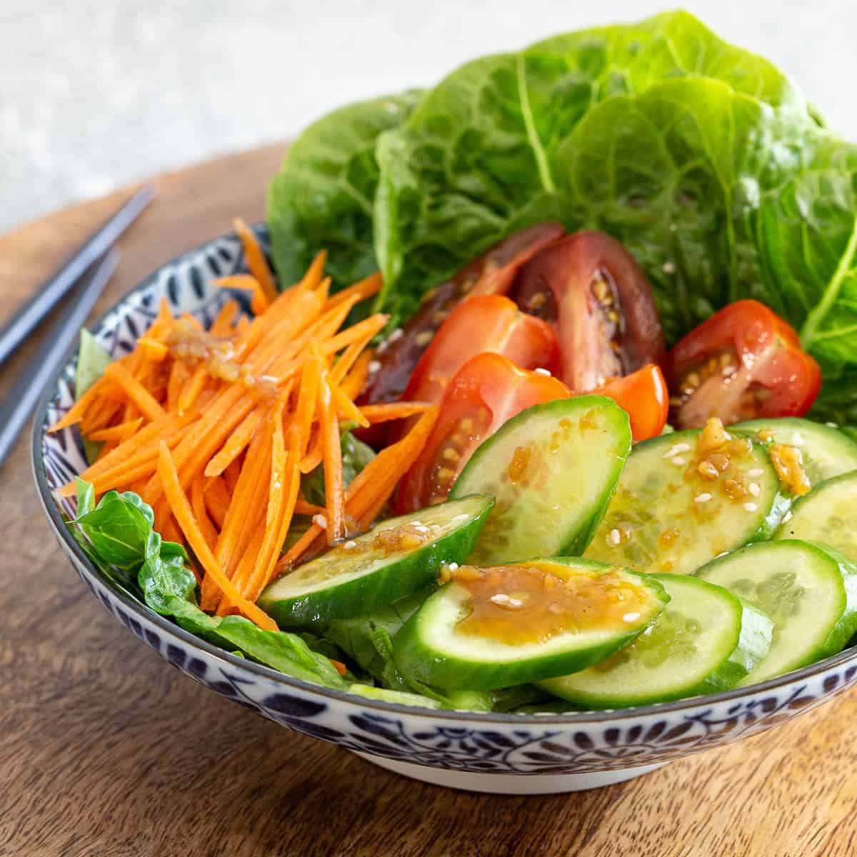 Prepared salad of cucumber, tomato, carrot and lettuce topped with wafu dressing.