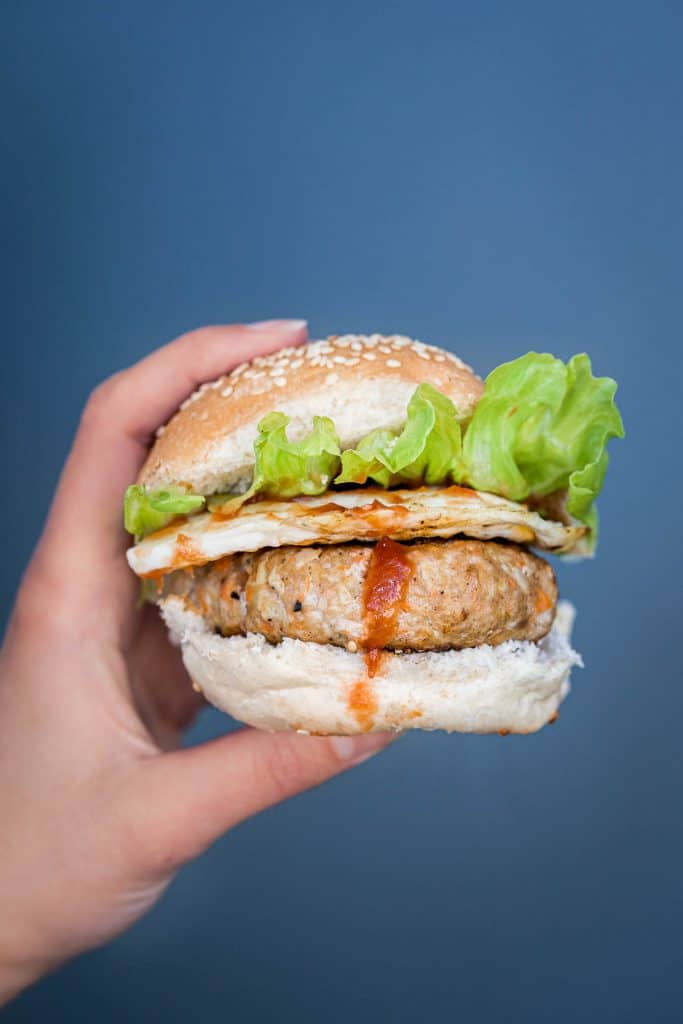 Hand holding a small pork burger with egg and lettuce on a sesame seed bun.