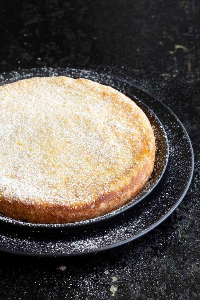 Whole lemon ricotta cake on black plates and dusted in sugar.