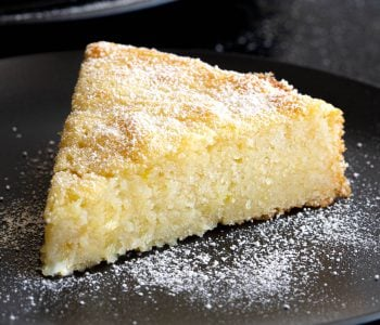 Slice of lemon ricotta cake on plate.