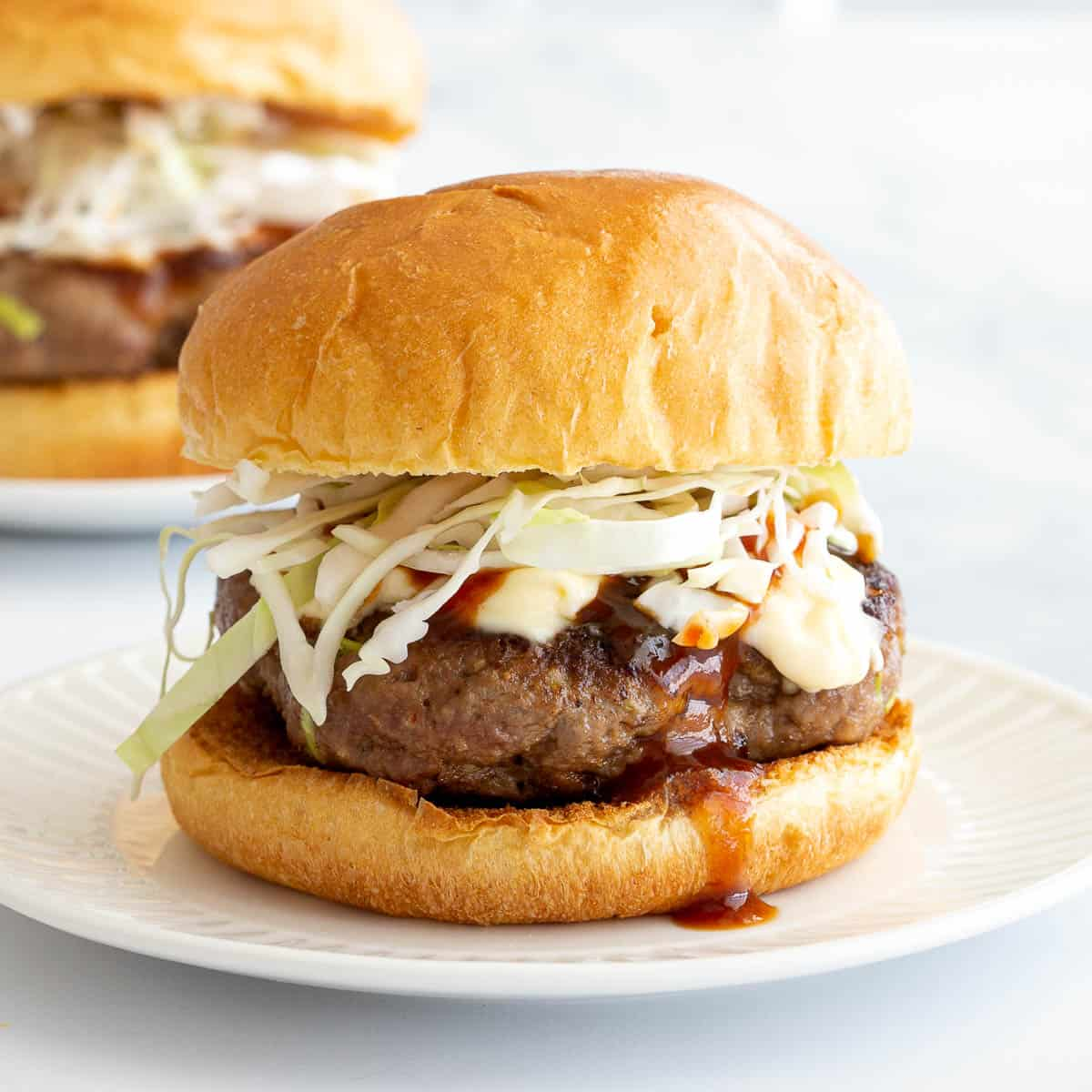Burger on a white plate dripping with bbq sauce.