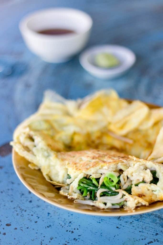 The finished lao omelette with the centre broken to show the wilted greens and bean shoots in the centre.