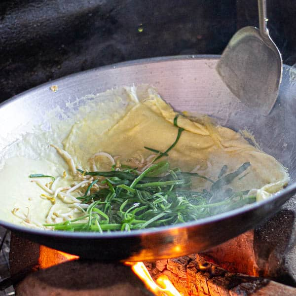 Pressing the edges of the omelette into the centre of the wok to fold them over the wilted greens.