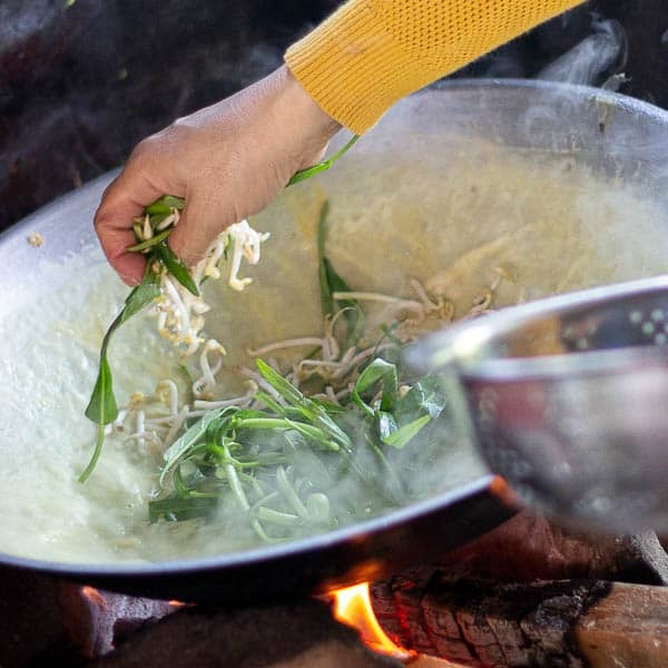 Adding bean shoots and greens on top of the egg batter as it cooks.