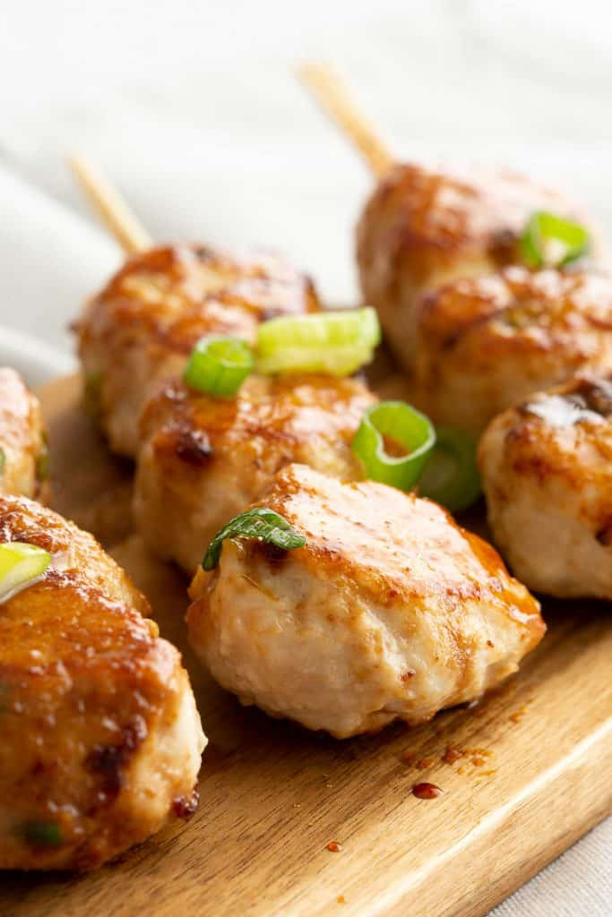 Shiny tsukune are coated in a teriyaki style sauce.