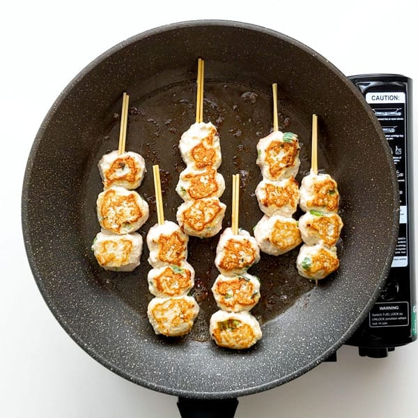 Frying the tsukune skewers.