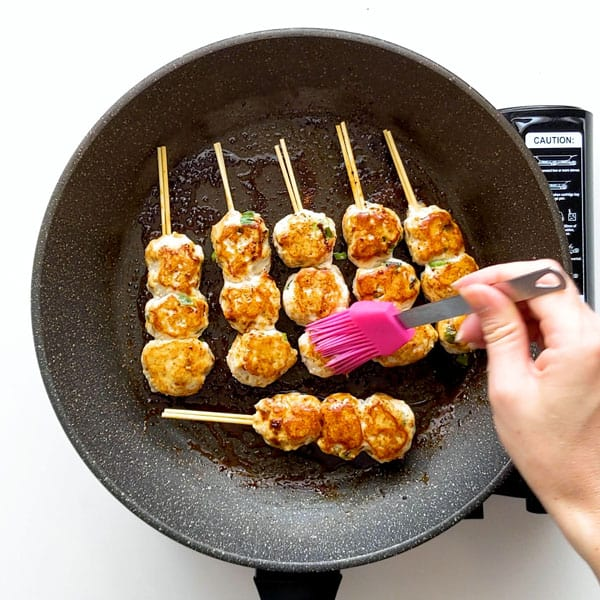 Basting the tsukune skewers with sweet soy sauce.