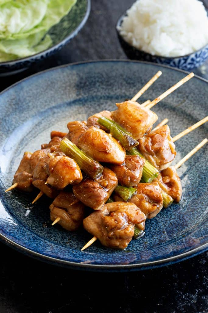 Pile of yakitori chicken skewers on plate with rice and cabbage in background.