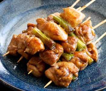 Blue plate with a stack of yakitori chicken skewers.