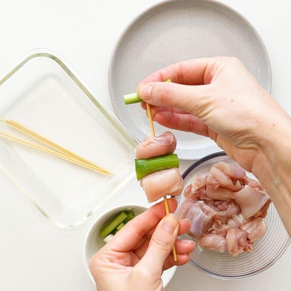 Threading spring onion onto a chicken skewer.