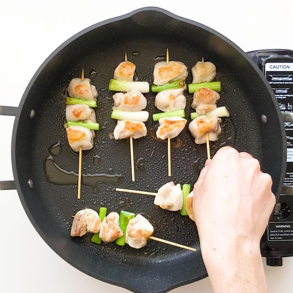 Flipping yakitori chicken skewers in a pan.