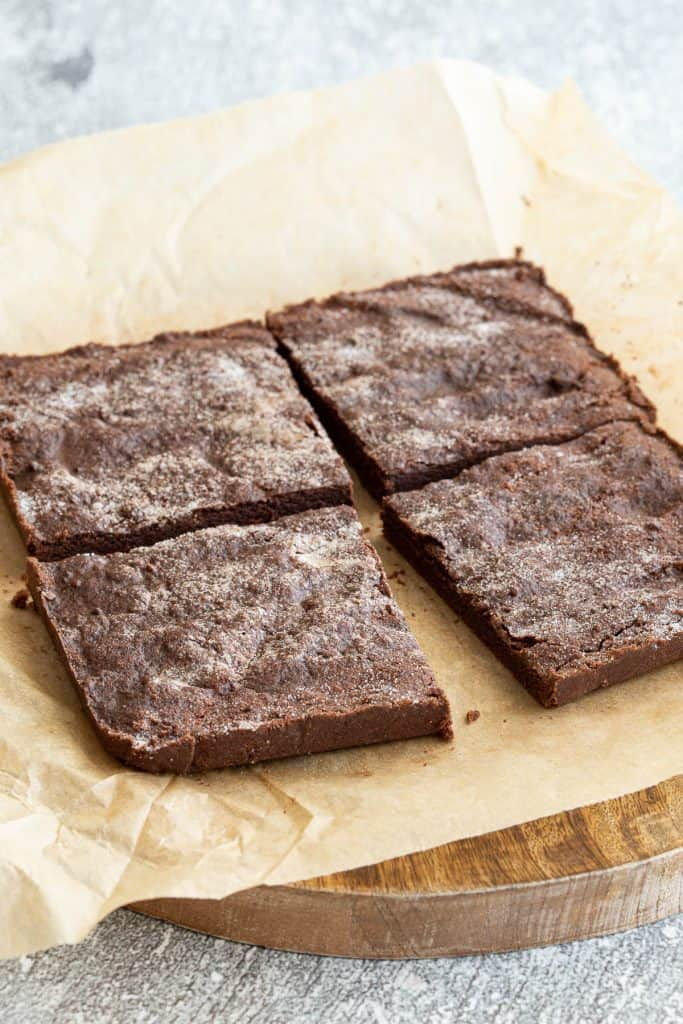 Four squares of chocolate concrete cake on baking paper.